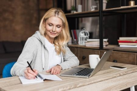 Photo for Smiling mature woman taking notes and using laptop at home - Royalty Free Image