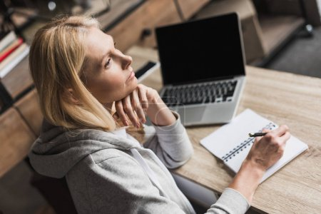 Photo for Pensive middle aged woman taking notes and using laptop at home - Royalty Free Image