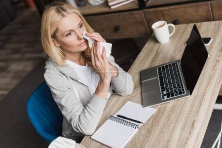 sick woman using laptop