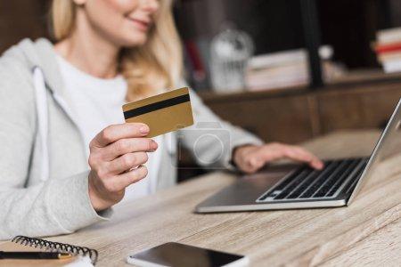 Photo pour Gros plan vue partielle de femme tenant la carte de crédit et à l'aide d'ordinateur portable à la maison - image libre de droit