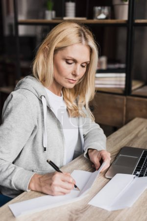 Photo for Serious middle aged woman writing on papers and using laptop at home - Royalty Free Image