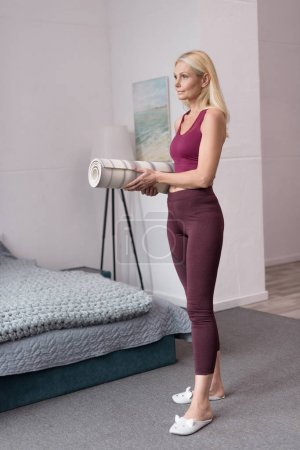 Photo for Full length view of beautiful sporty middle aged woman holding rolled yoga mat at home - Royalty Free Image