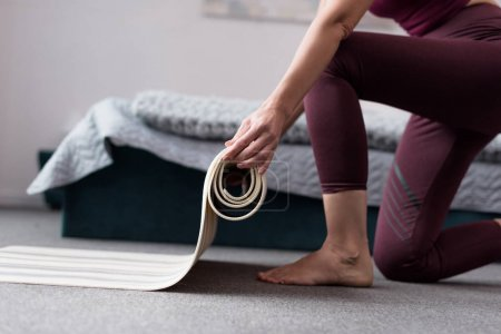 woman with yoga mat at home