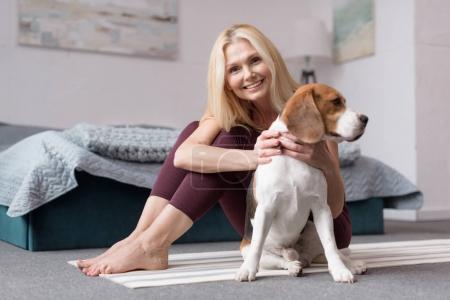 Photo pour Belle femme blonde souriant à la caméra tout en étant assis avec chien sur tapis de yoga - image libre de droit