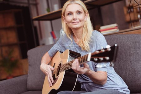 Photo for Beautiful smiling woman playing guitar and looking away at home - Royalty Free Image