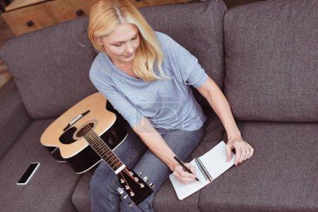 Photo pour Vue sur un angle élevé moyenne femme âgée avec la guitare, prendre des notes à la maison - image libre de droit