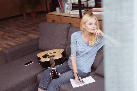 middle aged woman with guitar at home