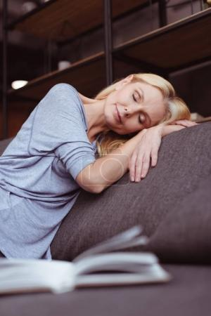 Photo for Attractive middle aged woman sleeping on sofa at home - Royalty Free Image