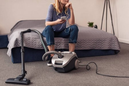 vacuum cleaner and woman with smartphone