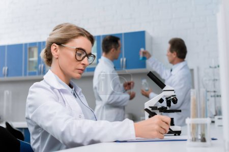 Photo for Professional lab technician in glasses, taking notes after doing microscope sample analysis - Royalty Free Image