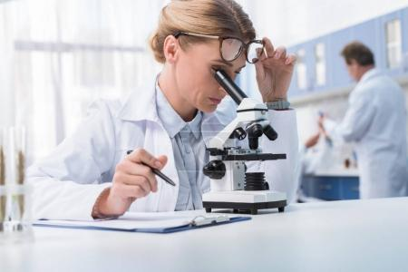 lab technician with microscope