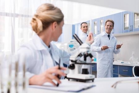 Photo pour Femme scientifique en blouse de laboratoire montrant une éprouvette avec échantillon à ses collègues souriants - image libre de droit
