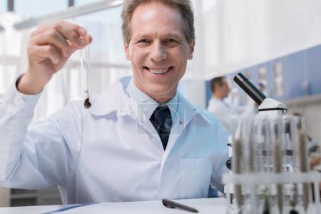 Photo for Smiling chemist in white coat holding test tube with sample and looking at camera in chemical lab - Royalty Free Image