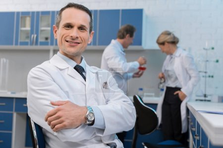 Photo for Smiling medical worker in laboratory, sitting with arms crossed and looking at camera while his colleagues are working behind - Royalty Free Image
