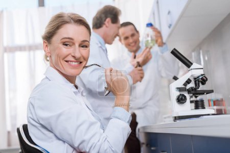 Photo for Smiling medical worker sitting in laboratory and looking at camera, while her colleagues are standing behind - Royalty Free Image