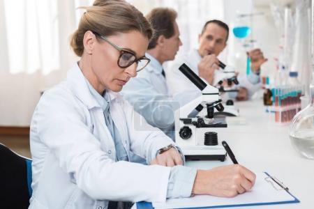 Photo pour Technicien laboratoire concentré en lunettes de vue, prendre des notes après avoir fait des analyses d'échantillons de microscope - image libre de droit
