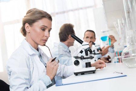 Photo pour Technicien de laboratoire songeur prendre des notes après avoir fait des analyses d'échantillons de microscope - image libre de droit