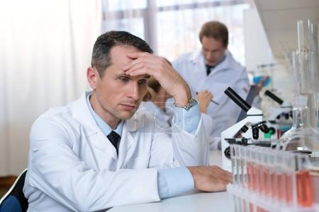 Photo for Stressed scientist sitting in laboratory during work, with hand on forehead - Royalty Free Image