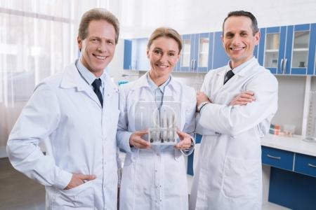 Photo pour Équipe de professionnels scientifiques en blouse blanche debout ensemble, tenant des tubes à essai et souriant à la caméra - image libre de droit