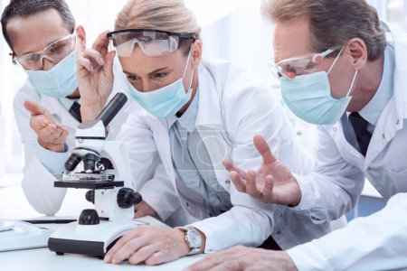 Doctors using microscope