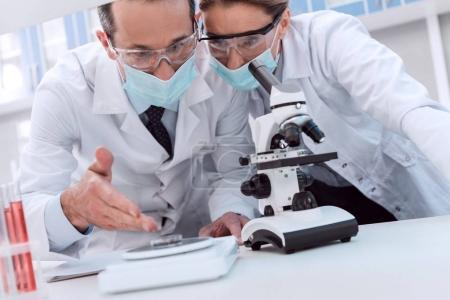 Photo for Professional scientists in white coats and sterile masks, using microscope and discussing work in laboratory - Royalty Free Image