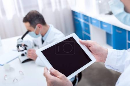 Photo for Cropped shot of lab technician in chemical laboratory, holding a digital tablet - Royalty Free Image