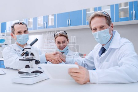 Photo for Doctors in lab coats and sterile masks, shaking hands and smiling, while looking at camera - Royalty Free Image
