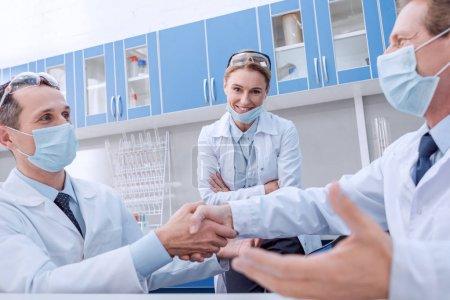 Photo pour Deux médecins de masques stérile, se serrant la main tandis que leur collègue est regardant et souriant - image libre de droit