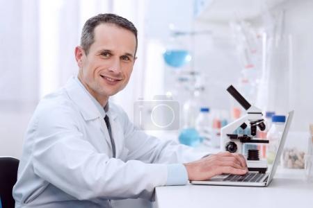 Photo pour Vue latérale du chimiste professionnel souriant, à l'aide de portable en laboratoire - image libre de droit