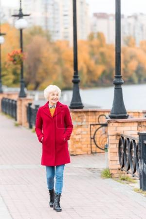 Photo for Senior smiling woman in red coat walking on quay - Royalty Free Image