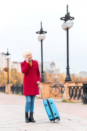 senior woman with suitcase and smartphone