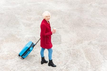 Photo pour Vue aérienne d'une femme senior avec café pour aller et sac de voyage - image libre de droit