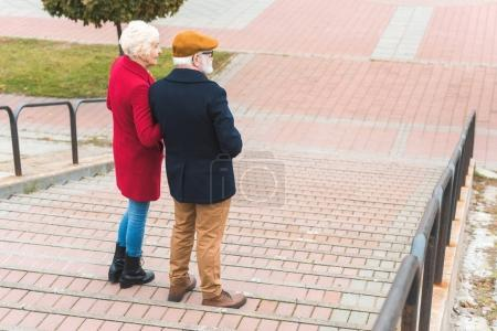 Photo for Back view of senior couple walking on stairs in city - Royalty Free Image
