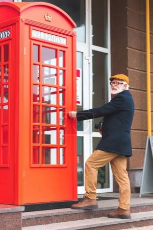 senior man at telephone box