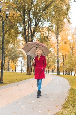woman with umbrella in autumn park