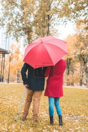Couple with umbrella in autumn park
