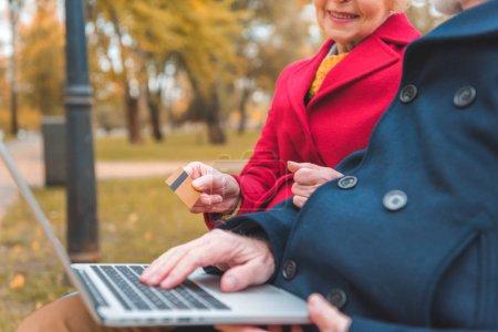 Photo pour Vue recadrée de couple shopping en ligne avec ordinateur portable et de carte de crédit en automne parc - image libre de droit