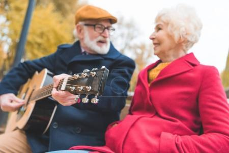 Photo for Happy senior couple playing on acoustic guitar in autumn park - Royalty Free Image