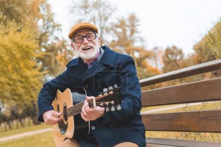 Photo pour Barbu élégant senior homme heureux jouant sur une guitare acoustique en automne parc - image libre de droit