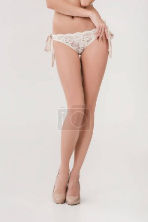 Photo for Low section of young woman in white lace panties and high heeled shoes posing isolated on grey - Royalty Free Image