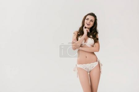 Photo for Thoughtful young woman in white lace lingerie smiling and looking away isolated on grey - Royalty Free Image