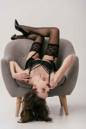 Photo for Seductive young woman in black lingerie and stockings lying upside down on armchair isolated on grey - Royalty Free Image