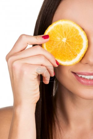 woman covering eye with slice of orange