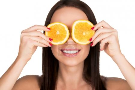 woman covering eyes with sliced orange