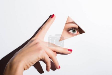 Photo for Beautiful woman looking out of hole in white paper and touching it with hand - Royalty Free Image
