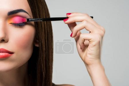 woman applying colorful eyeshadows