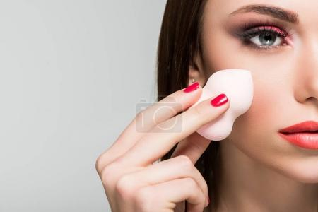 woman doing makeup with cosmetic sponge