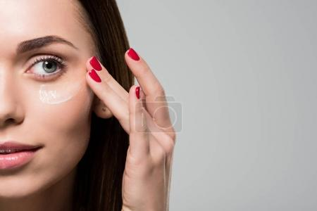 Photo for Young woman applying facial moisturizing cream isolated on grey - Royalty Free Image