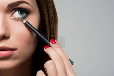 woman doing makeup with cosmetic pencil