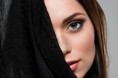 woman covering face with black cloth